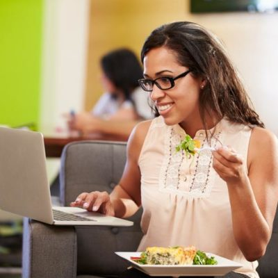 woman in office with computer eating salad for lunch