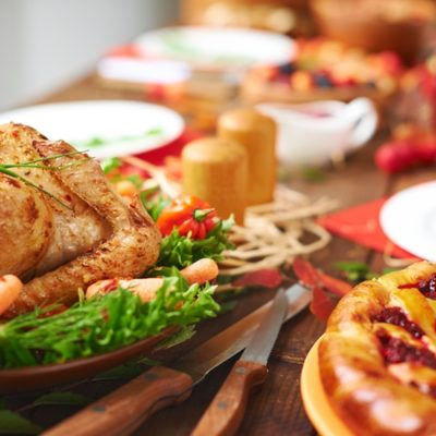 Thanksgiving table with roasted turkey and other food