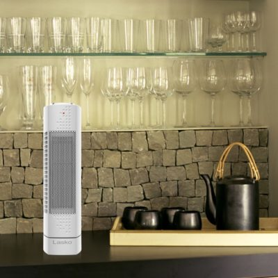 Lasko, Ultra-Slim Ceramic Tower Heater Model CT14102, on table with glasses