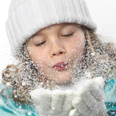 A young girl blows snow off of her gloves