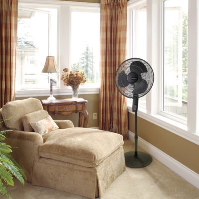 sun room with windows, lounge chair and Lasko black pedestal fan