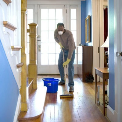 Man with face mask washing wood floor