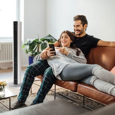 young couple relaxing near Lasko Tower Fan and Space Heater, Model FH500
