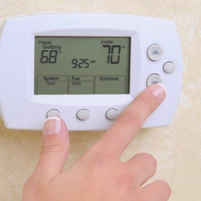 person's hand adjusting home thermostat