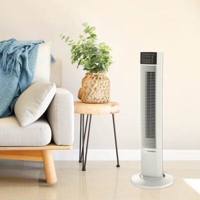 white couch next to Lasko Wind Tower Fan with Remote Control, model T36610