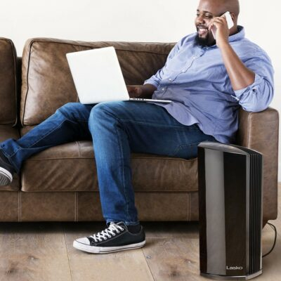 Man working on couch next to Lasko HEPA FIlter Air Purifier model LP450