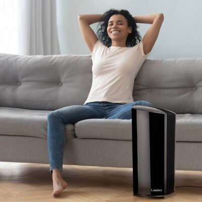 Woman relaxing on couch and enjoying fresh air next to Lasko LP450 HEPA Air Purifier
