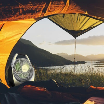 inside a camping tent looking outdoors at scenery and Lasko Battery Fan model RB200